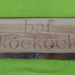 Gefreesde tekst uit larikshout